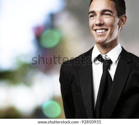 portrait of business man smiling against a lights background