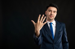 Portrait of business man wearing blue business suit and tie showing five fingers isolated on black background with copy space advertising area
