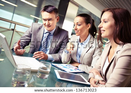 Portrait of business partners pointing and looking at laptop display at meeting