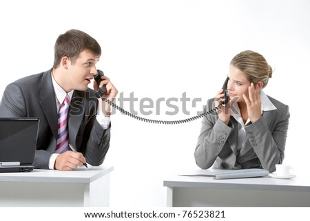Portrait of business partners speaking on the telephone and looking at each other
