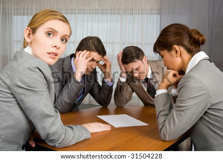 Portrait of business people sitting around table and brainstorming while one female looking at camera