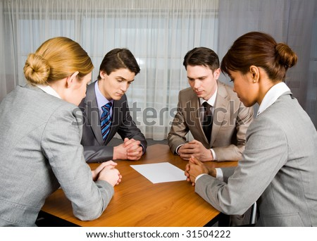 Portrait of business people sitting around table and looking at blank paper in center