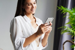 Portrait of business woman, holds smartphone in her hands. Beautiful girl uses mobile phone for work, calls clients, sends text messages. Millennial girl in white shirt stands against white wall