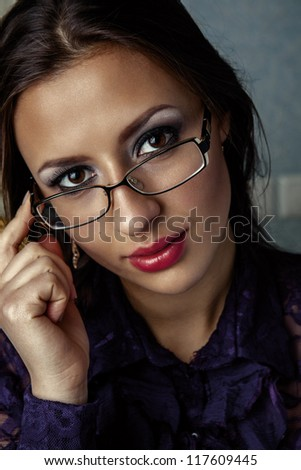 Portrait of business woman in glasses. A look through the glasses