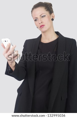 Portrait of business woman looking angrily in phone , isolated on white background