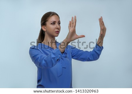 Portrait of business woman on gray background in studio. Layout to create virtual technology, spread hands gesture