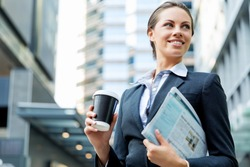 Portrait of business woman walking and smiling outdoor