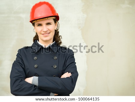 Portrait of business woman wearing protection helm against the new building wall