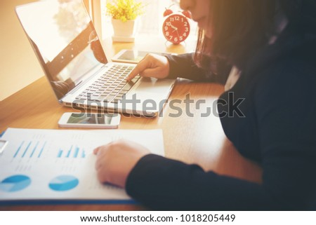 Portrait of business woman with laptop, finance graph and writes on a document at her office. - Shutterstock ID 1018205449