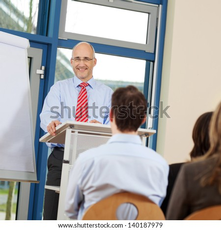 Portrait of businessman giving presentation to coworkers while standing at podium in office