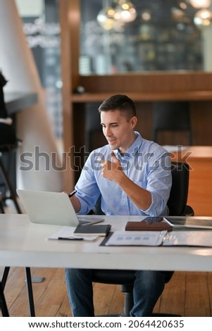 Portrait of businessman having a online meeting, video conference, online webinar with client via laptop computer in his office.