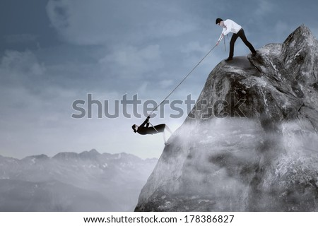 Portrait of businessman help his partner to climb the cliff by pulling her with a rope
