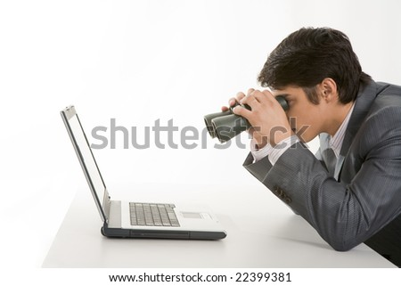 Portrait of businessman holding binoculars and looking at laptop