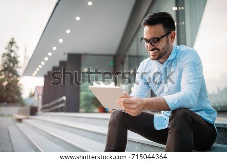 Portrait of businessman in glasses holding tablet #715044364