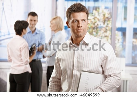 Portrait of businessman in office, holding notepad. Colleagues talking in the background.