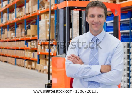Portrait Of Businessman In Warehouse With Fork Lift