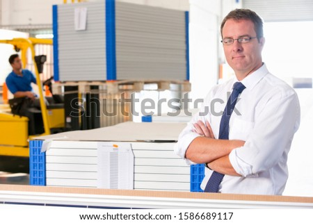 Portrait of Businessman looking at camera supervising forklift truck driver in solar panel factory warehouse