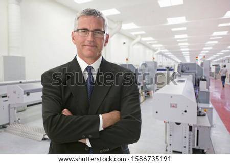 Portrait Of Businessman On Floor Of Engineering Factory