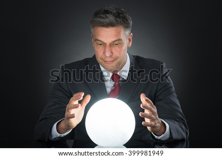 Portrait Of Businessman Predicting Future With Crystal Ball On Desk #399981949
