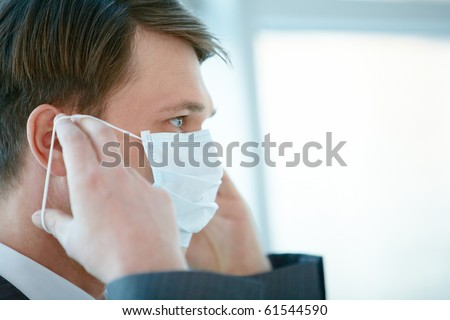 Portrait of businessman putting protective mask on his face