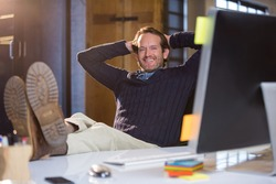 Portrait of businessman rseting at computer desk in creative office
