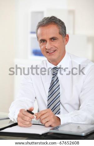 Portrait of businessman sitting at his desk