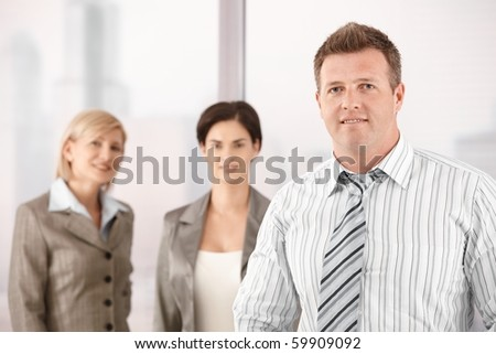Portrait of businessman smiling at camera, with female coworkers in background?