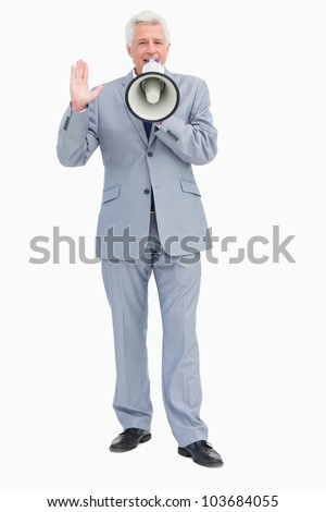 Portrait of businessman speaking with megaphone against white background