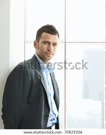 Portrait of businessman standing at office window, looking at camera, smiling.?