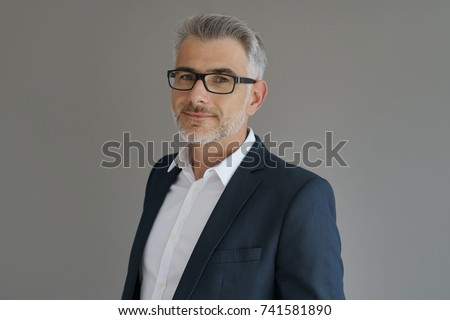 Portrait of businessman standing on grey background, isolated
