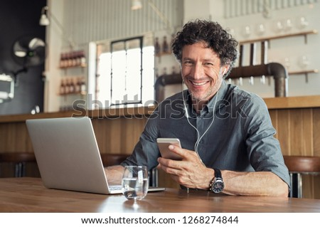 Portrait of businessman using smartphone with earphones and laptop. Smiling business man sitting in restaurant listening to music. Happy man enjoying free wireless internet connection at coffee shop.