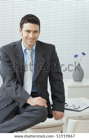Portrait of businessman wearing grey suit and blue shirt, sitting on office desk, smiling.