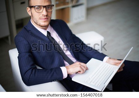 Portrait of businessman with laptop looking at camera in office