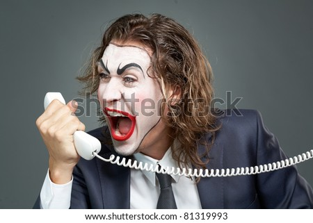Portrait of businessman with painted face shouting at telephone receiver