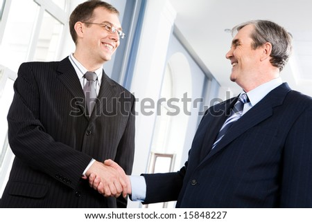 Portrait of businessmen shaking hands greeting each other in the corridor