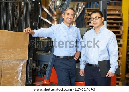 Portrait Of Businessmen With Fork Lift Truck In Warehouse