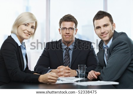 Portrait of businesspeople at office meeting looking at camera sitting at table.