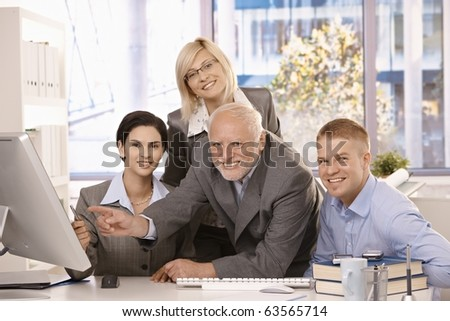 Portrait of businessteam at work, pointing at computer screen, looking at camera, smiling, senior executive in middle.?