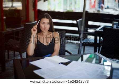 portrait of businesswoman in eyeglasses making notes in notebook at table in restaurant. Woman thinks, holds a pen by the temple. Thoughts New ideas. Blogging