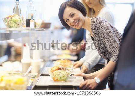 Portrait of businesswoman in lunch line at work cafeteria