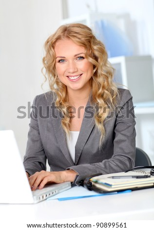 Portrait of businesswoman in office working on laptop computer
