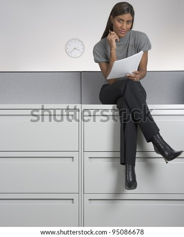 Portrait of businesswoman sitting on filing cabinet