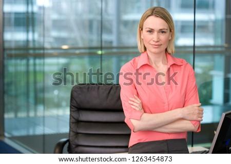 Portrait of businesswoman standing by desk in office