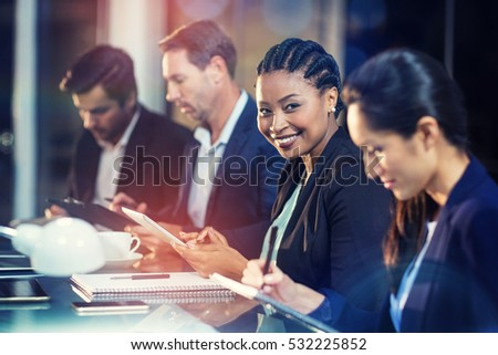 Portrait of businesswoman using digital tablet while colleagues writing notes in office