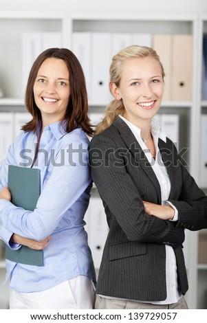 Portrait of businesswomen standing back to back in office