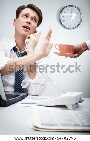 Portrait of busy chief calling by phone and refusing from cup of coffee held by his secretary