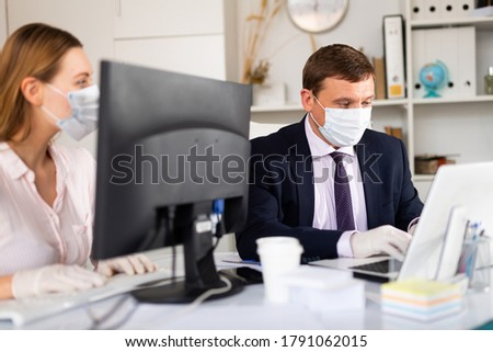 Portrait of busy entrepreneur in medical face mask and latex gloves working with female coworker in office. Concept of precautions and social distancing in coronavirus pandemic
