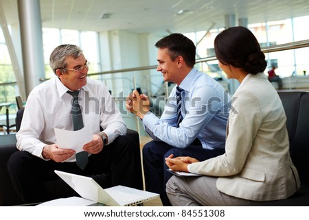 Portrait of busy people discussing new strategies and ideas at meeting