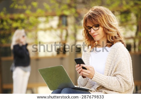Portrait of busy sales woman sitting at business park and using her laptop while writing text on mobile. Businesswoman working online.