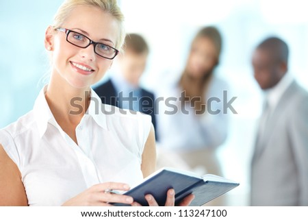 Portrait of busy secretary with notepad looking at camera in working environment